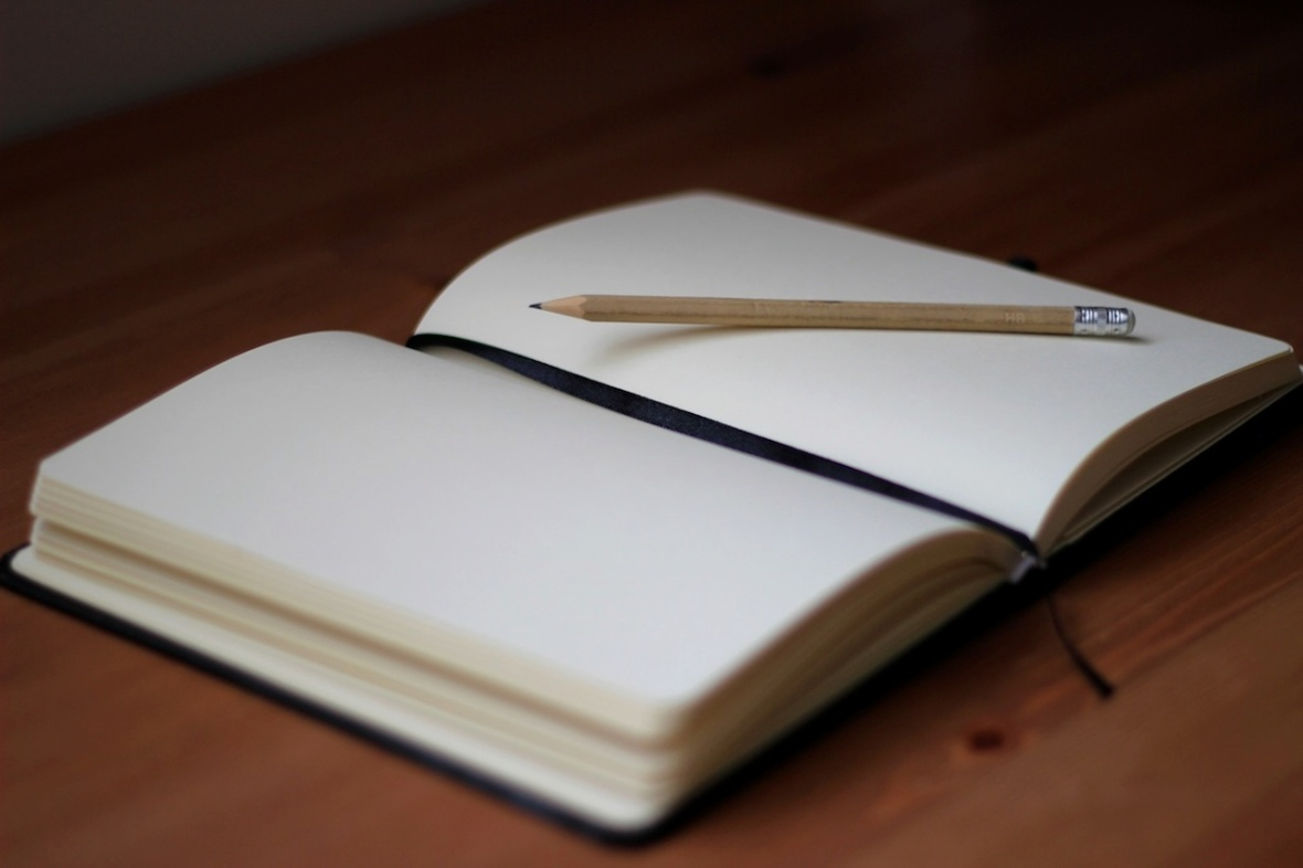 empty notebook sitting open on desk with a lead pencil lying on top of it
