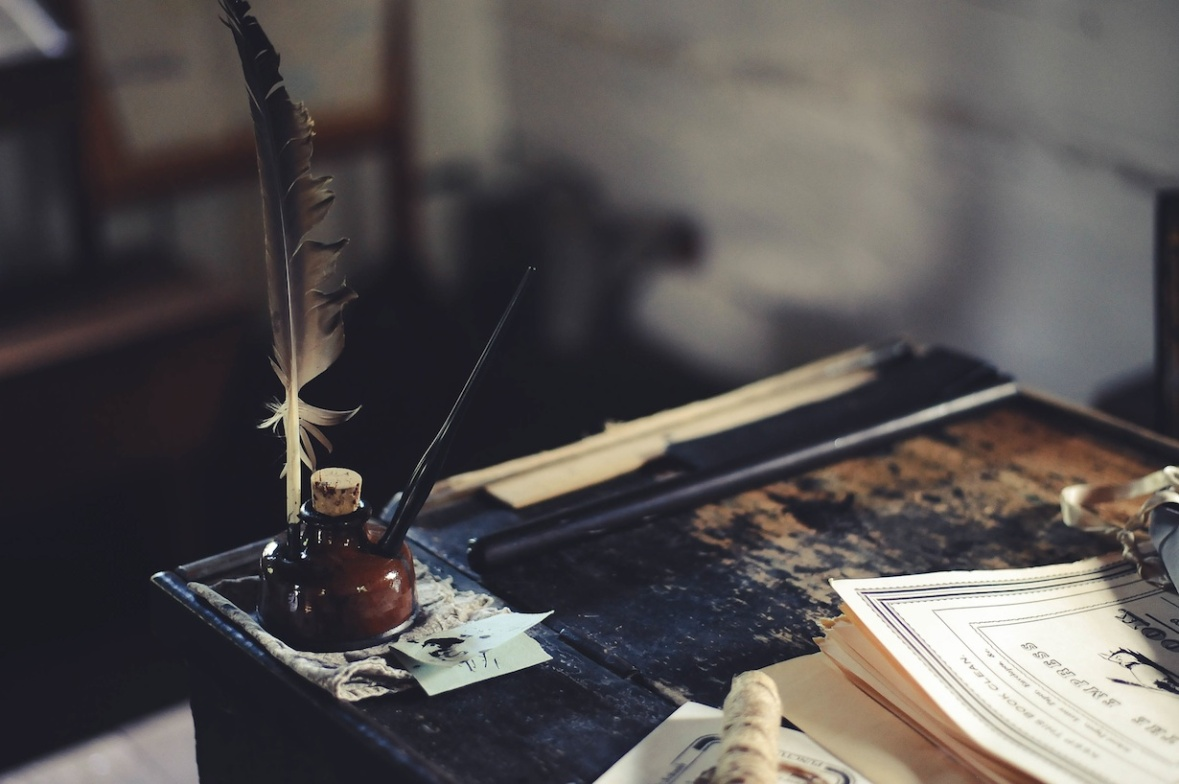 inkwell and feather pen on writing table
